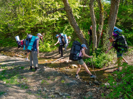 Hikers group crossing a brook photo