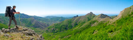 Hiker on the top enjoys panorama landscape 写真素材