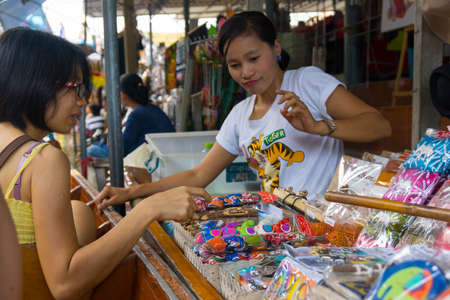 ratchaburi: RATCHABURI, THAILAND - MARCH 24: Local peoples sell fruits, food and souvenirs at famous tourist attraction Damnoen Saduak floating market on March 24, 2014 in Ratchaburi, Thailand.
