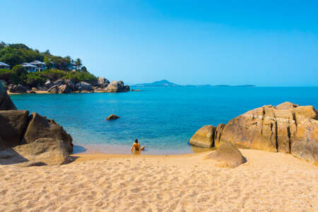 Young woman relaxes on the rocky beach in Thailand Stock Photo - 27916105