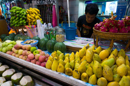 BANGKOK, THAILAND - MARCH 22: A street vendor sells fresh fruits and shakes to tourists at famous backpackers destination Khao San Road at night on March 22, 2014 in Bangkok, Thailand.