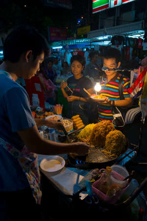 BANGKOK, THAILAND - MARCH 22: A street vendor sells traditional Thai food to tourists at famous backpackers destination Khao San Road at night on March 22, 2014 in Bangkok, Thailand.