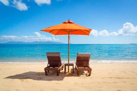 해변에 태양 우산과 라운지 의자 두 개