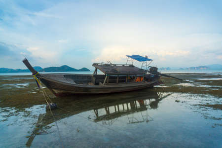 Traditional longtail boat at low tide in Thailand photo