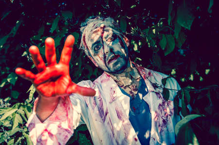 Man zombie walking dead outdoors. Dark lighting. Color was changed to emphasize the atmosphere of horror. photo