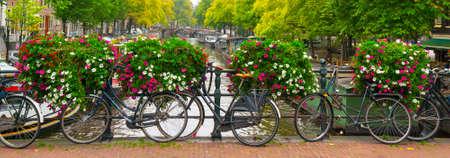 Traditionelle holländische Fahrräder auf Kanal in Amsterdam geparkt Standard-Bild - 34008671