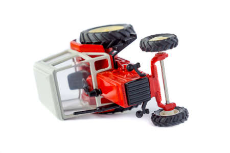 Toy tractor lying on its side isolated model on white photo