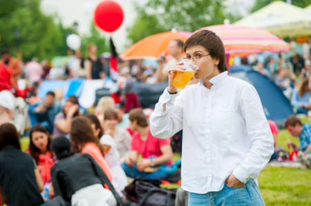 international beer: MOSCOW - JUNE 20, 2015: Young woman drinks beer on XII International Jazz Festival Usadba Jazz in Tsaritsyno Park on June 20, 2015 in Moscow