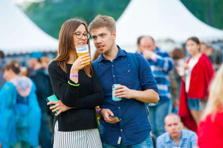 international beer: MOSCOW - JUNE 20, 2015: Young couple drink beer on XII International Jazz Festival Usadba Jazz in Tsaritsyno Park on June 20, 2015 in Moscow