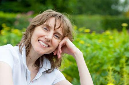 Lachende middelbare leeftijd vrouw portret in een park