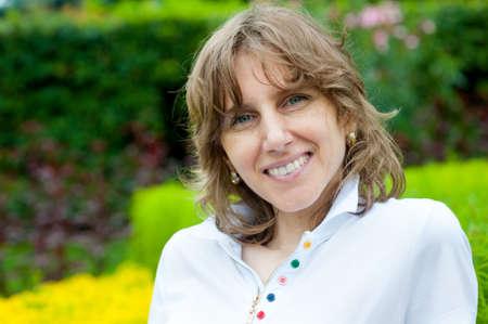 edad media: Retrato sonriente mujer de mediana edad en un parque