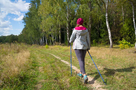 Young woman goes Nordic walking outdoors. Back view photo
