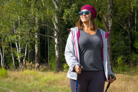 Young woman goes Nordic walking outdoors photo