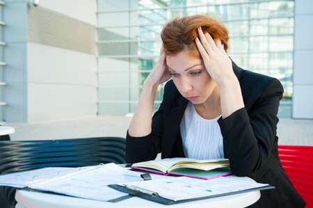 agotado: Mujer de negocios frustrada y cansada sentado en fondo moderno