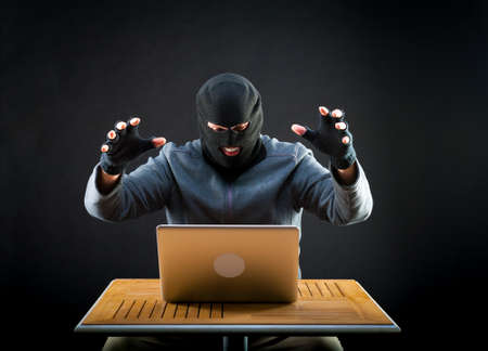 cyber crime: Hacker is ready to start hacking laptop Stock Photo