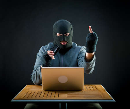 stolen: Hacker holding stolen credit card and showing middle finger Stock Photo