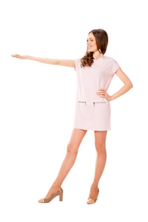outstretched hand: Young slim pretty woman in pink dress with outstretched hand isolated on white background