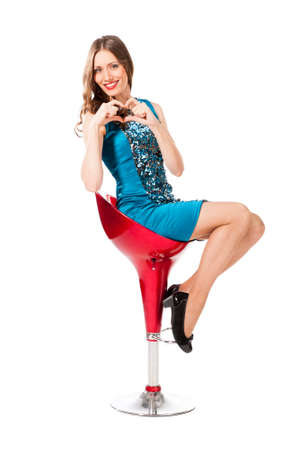 bar chair: Young slim pretty woman in blue dress with sequins posing on bar chair isolated on white background