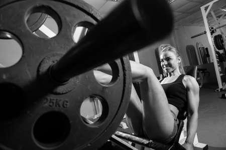 Mujer muscular joven que hace ejercicio en el gimnasio