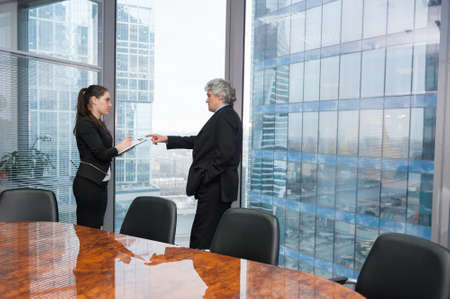 instructs: Boss instructs young secretary in modern office