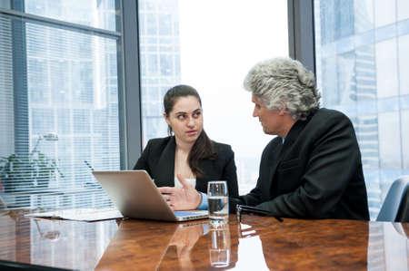 Dojrzały biznesmen i młoda biznesowa kobieta rozmawiają w nowoczesnym biurze