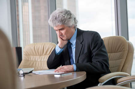 docs: Mature business man works with docs in modern office Stock Photo