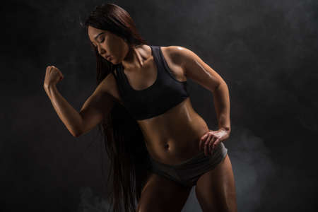 asian bodybuilder: Young muscular asian woman posing on black background