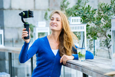 live action: Young pretty woman broadcast live video using action camera and gimbal
