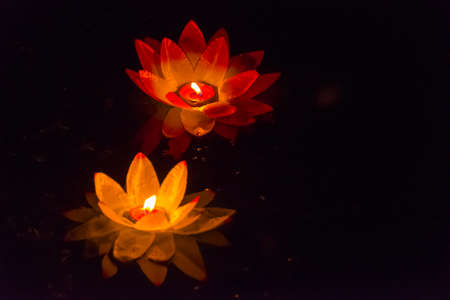 Floating paper lanterns on the water at night Stock Photo