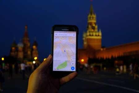 Moskou, Rusland - 31 juli: Mannelijke hand met een smartphone met een lopende Google maps-app op de achtergrond van Red Square-monumenten