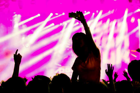 Fan using mobile device for taking pictures, videos or broadcasting at concert Stock Photo
