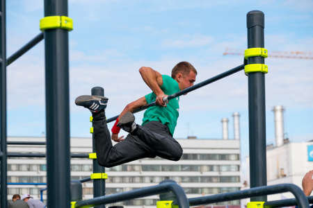 calisthenics: Moscow, Russia - September 10, 2016: Young man practice street workout on open competition dedicated to City Day