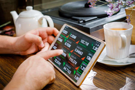 Business man works with foreign exchange rates on tablet pc in cafe