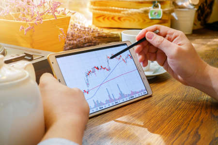 stylus: Business man works with graph on tablet pc with stylus in cafe