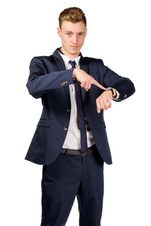 Young businessman dressed in a suit points to at watch isolated on white Stock Photo