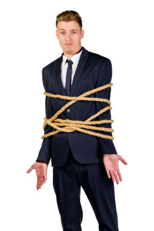 tied in: Young businessman in a suit tied up with rope