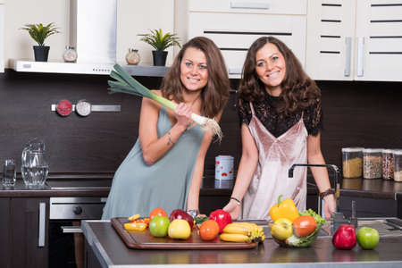 twin house: Two twin sisters having fun in the morning preparing breakfast in the kitchen