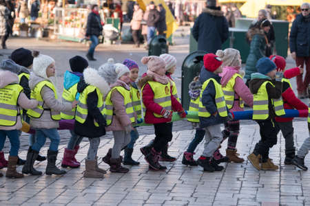elementary schools: Krakow, Poland - December 16, 2016: Children age 6-7 years wlaking in a row on the street