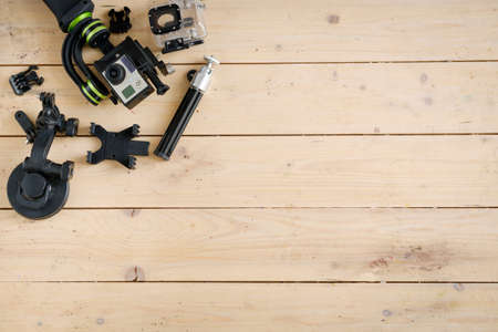 stabilizer: Action camera on the wooden table with a stabilizer and other accessories
