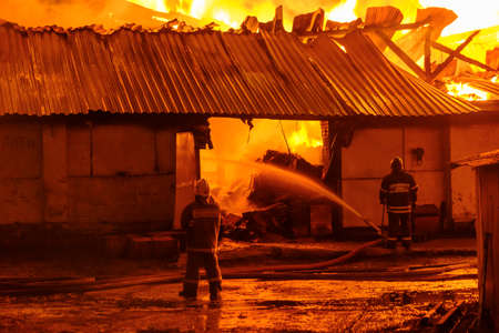 Firefighters extinguish a fire in a burning warehouse