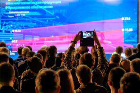 남자는 스마트 폰을 사용하여 컨퍼런스 홀에서 프리젠 테이션 사진을 찍는다.