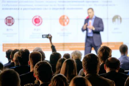 聴衆は会議場で講師に耳を傾ける