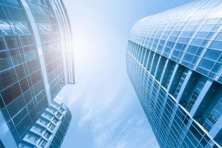 Vista inferior del barrio moderno de la ciudad en tonos azules con brillo solar