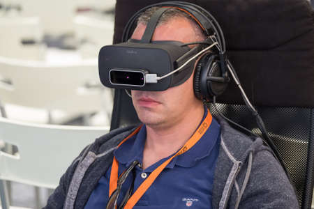 Moscow, Russia - June 8, 2017: VR conference visitor tests virtual reality helmet