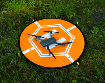 Quadcopter at the landing pad on the grass Stock Photo