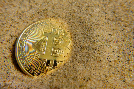 Golden bitcoin coin in the sand Zdjęcie Seryjne