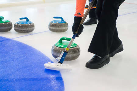 Team members play in curling at championship Фото со стока