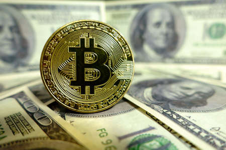one hundred dollars: Golden bitcoin coin on the one hundred dollars banknote. Macro. Cryptocurrency concept