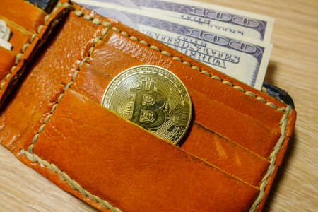 Golden bitcoin coin in the leather wallet top viev 写真素材