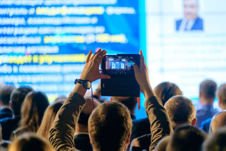 Man takes a picture of the presentation at the conference hall using smartphone Reklamní fotografie